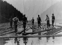 Men standing on logs in the river.